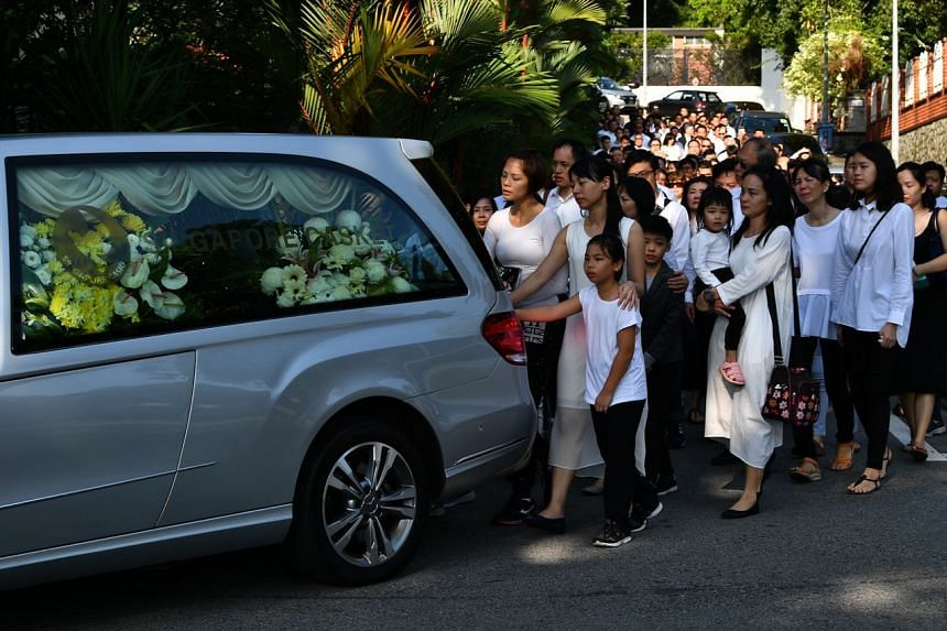 Mr Ben Goi's wife, Malaysia-born former TV actress Tracy Lee (centre), walking behind the hearse as it leaves for Mandai Crematorium.