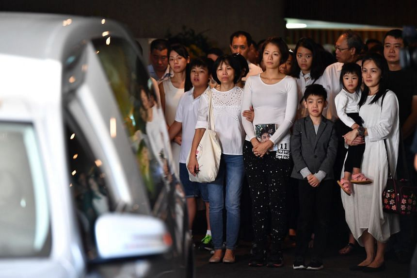 Mr Ben Goi's wife, Ms Tracy Lee (centre), holds his a photo of him as his coffin is being carried into the hearse.