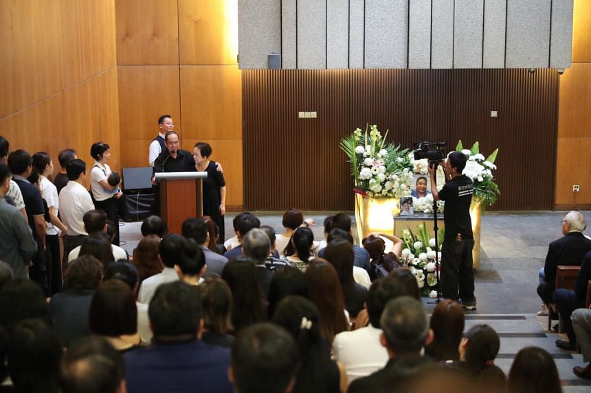 Mr Sam Goi stands with his wife as he gives a eulogy at their son's funeral service in Mandai.