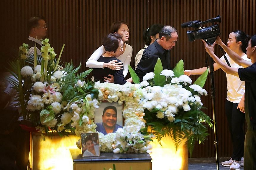Mr Ben Goi's parents, Sam and Jacqueline Goi (both centre, in black), and wife, Ms Tracy Lee (embracing Mrs Goi), at the funeral service in Mandai Crematorium yesterday.