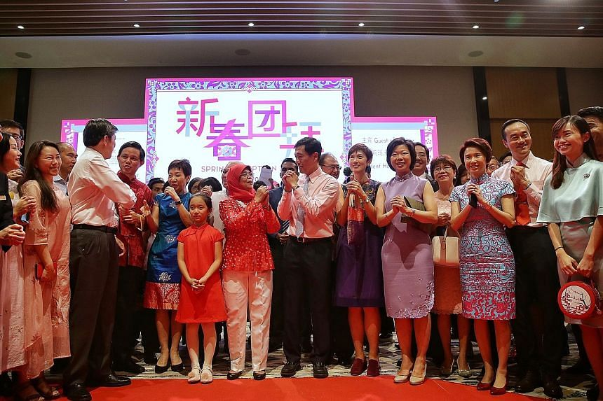 President Halimah Yacob, with 11-year-old Yu Neng Primary School pupil Alexis Foo, exchanging Chinese New Year greetings with other guests at the spring reception at the Singapore Chinese Cultural Centre yesterday. With them were (from left) Minister