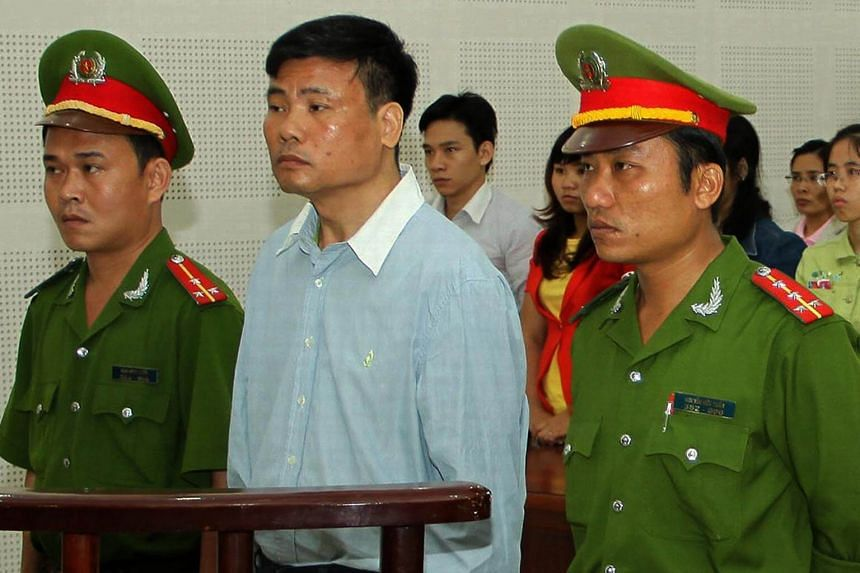 Blogger Truong Duy Nhat (centre) stands trial at a local People's Court in the central Vietnam city of Da Nang, on March 4, 2014.