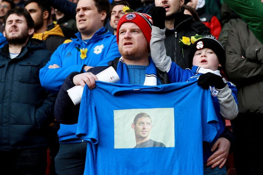 A Cardiff City fan holds a shirt in remembrance of Emiliano Sala before the match against Southampton.