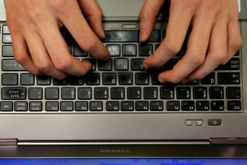 Posed photo of a person using a laptop keyboard.