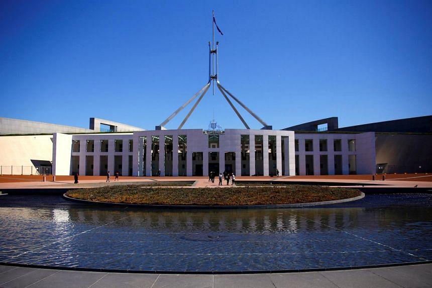 Tourists walk around the forecourt of Australia's Parliament House in Canberra, on Oct 16, 2017.