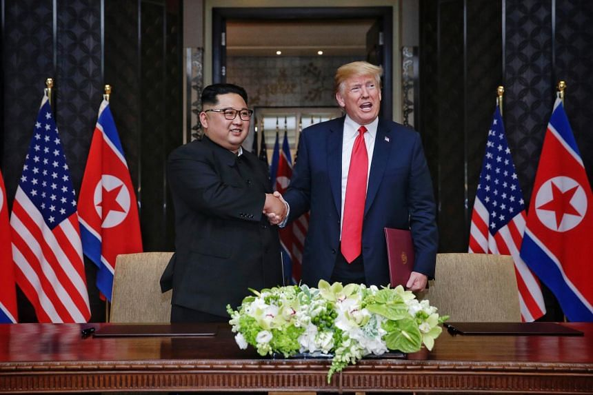 North Korean leader Kim Jong Un smiles as he shakes hands with US President Donald Trump during the signing of the declaration, after their first summit meeting in Singapore on June 12, 2018.