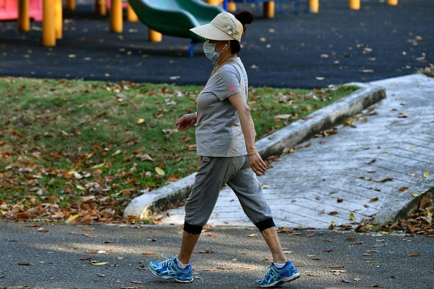 A brisk walker wearing a face mask while walking at Tampines Central Park on Feb 8, 2019.