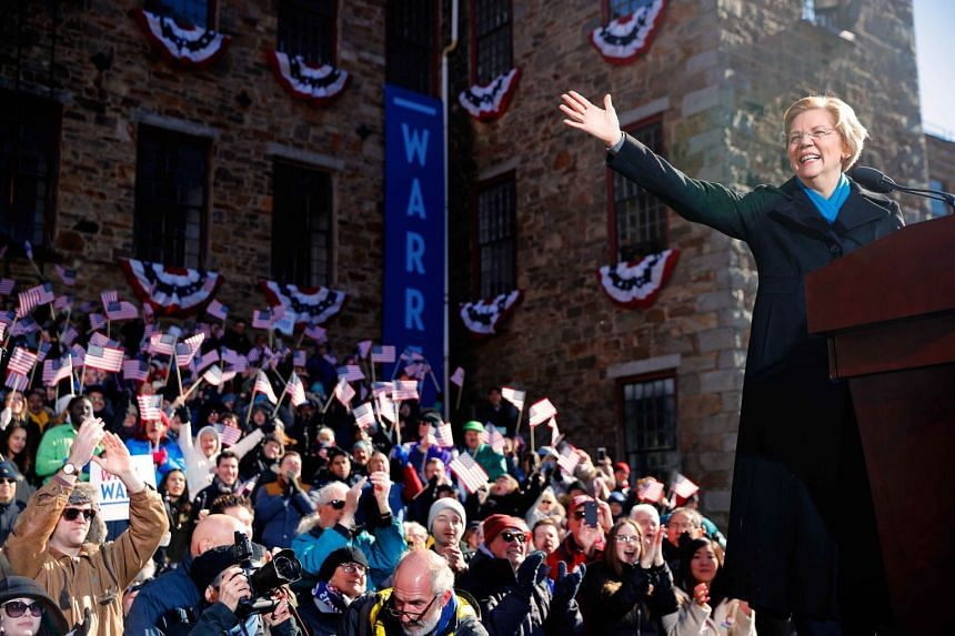Elizabeth Warren waves at the crowd ahead of a campaign rally in Lawrence, Massachusetts.