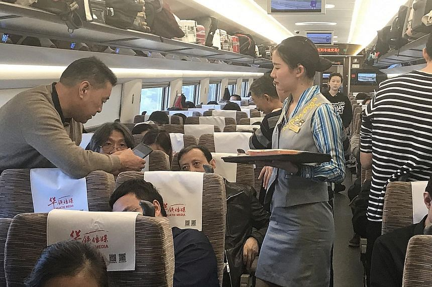 A passenger paying for his food using a mobile phone. Attendants on China's high-speed trains prefer passengers to scan a QR code, which can be found at every seat, with their phones to pay or to order food. Travellers can get an array of snacks, hot