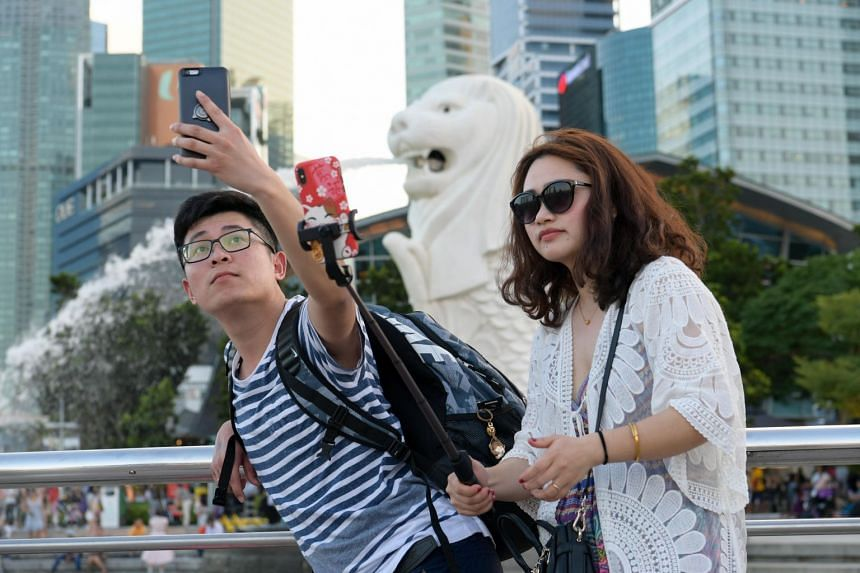 Tourists taking photos at the Merlion Park on Feb 12, 2018. A booming tourism industry is driving China's demand for professional tour guides around the world.
