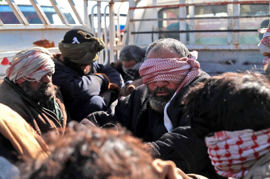 Alleged ISIS group fighters who fled from the frontline Syrian village of Baghuz, near the Iraqi border, sit blindfolded in the back of a pickup truck after being taken into custody by SDF forces for screening.