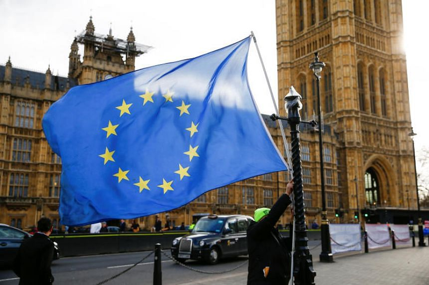 An anti-Brexit protester tying an EU flag to a lamp post outside the Houses of Parliament in London on Feb 7, 2019.