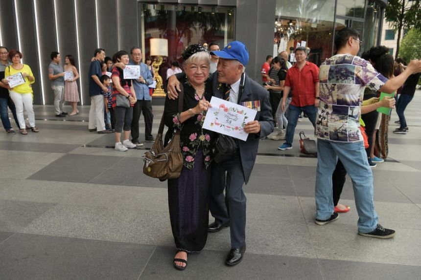 """Mr William Wee and his wife Nancy posing as part of a """"freeze mob"""" outside ION Orchard on Feb 10, 2019."""
