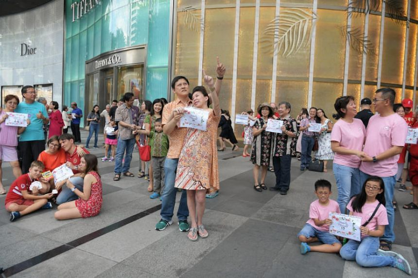 """Couples and families """"freezing"""" for five minutes outside ION Orchard on Feb 10, 2019."""