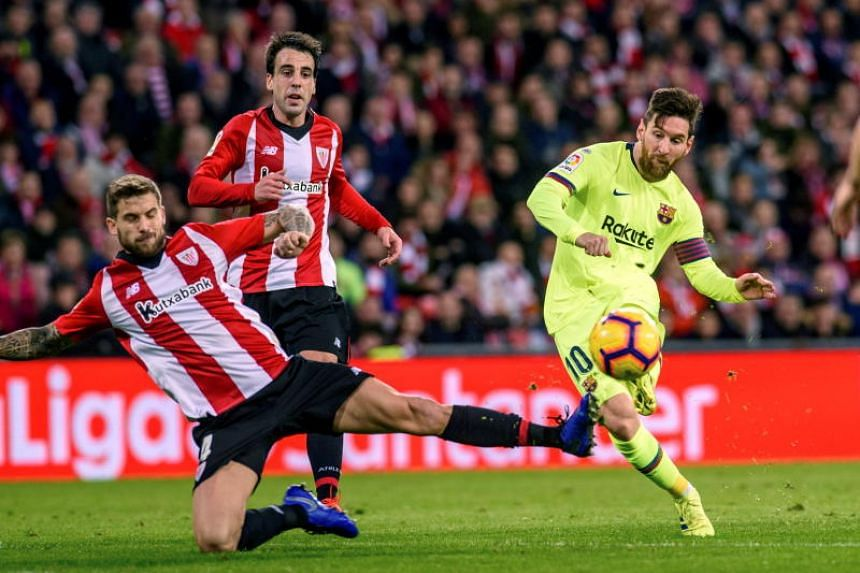 FC Barcelona's Lionel Messi (right) in action against Athletic Bilbao's Inigo Martinez during a Spanish La Liga match between Athletic Bilbao and FC Barcelona at San Mames stadium in Bilbao, northern Spain, on Feb 10, 2019.