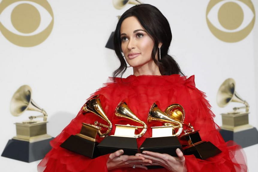 US singer-songwriter Kacey Musgraves poses with the Grammy for Best Country Album, Best Country Song, Best Country Solo Performance, and Album of the Year during the 61st annual Grammy Awards ceremony at the Staples Center in Los Angeles, California