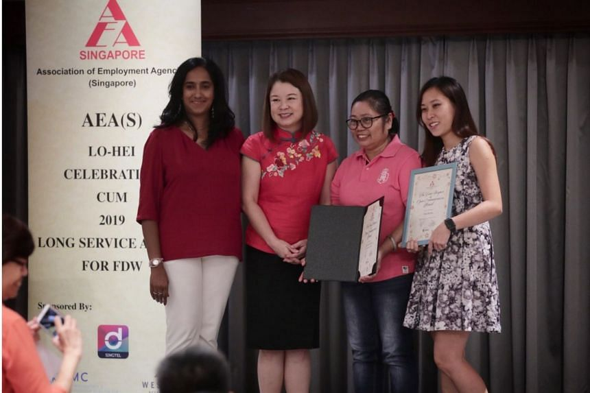 Foreign domestic worker Maria Aida Procalla Somejo (in pink), who has worked in Singapore for 28 years, receiving the Long Service Award at Holiday Inn Singapore Atrium.