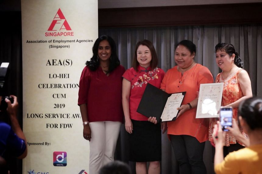 Naw Wah Wah (second from right ), who has worked in Singapore for 11 years, receiving the Long Service Award.