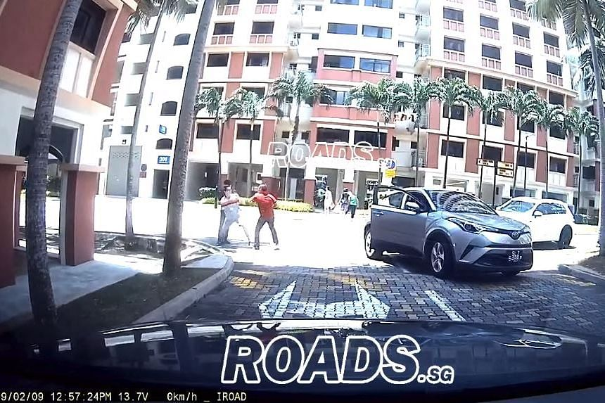 The video shows the driver confronting a man, who adopts a fighting stance. Both men fall to the ground after trading blows.