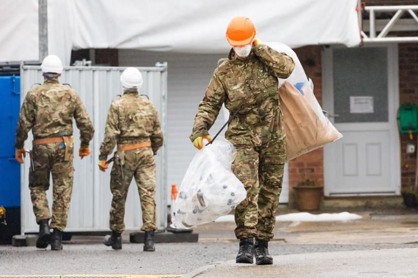 Army officers seen carrying bags after removing what is believed to be part of the roof at the house of former Russian spy Sergei Skripal in Salisbury, Britain, on Feb 4, 2019.