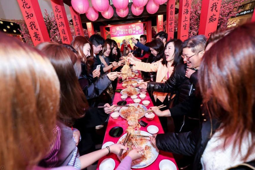 Staff of Crystal Galleria, a shopping mall in downtown Shanghai, representatives from the Singapore Chinese Cultural Centre and local shoppers partaking in lohei on Feb 11, 2019.