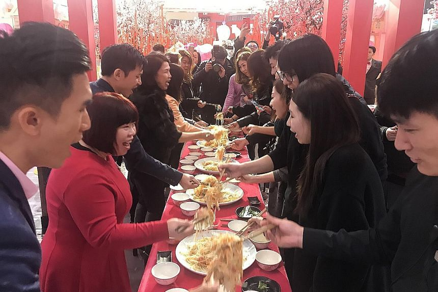 Shoppers and staff of Crystal Galleria, a mall in downtown Shanghai, joining the Singapore Chinese Cultural Centre (SCCC) delegation in tossing yusheng - or lo hei - yesterday, the seventh day of the Chinese New Year. The custom of eating raw fish is