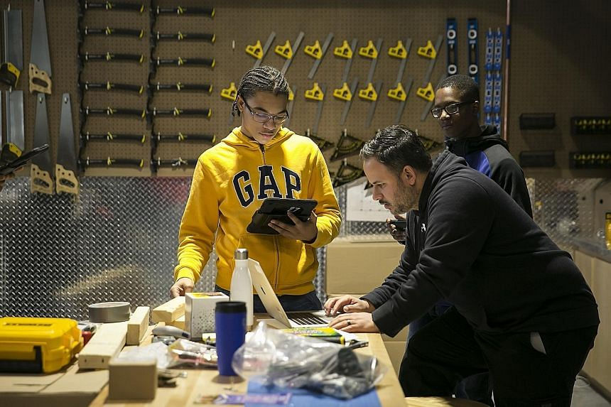 Instructor Mitchell Almonte (foreground) works with students during a construction technology class at the Brooklyn Steam Centre.