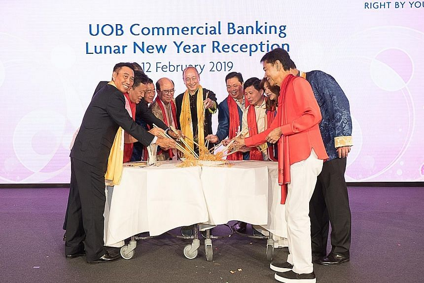 UOB deputy chairman and CEO Wee Ee Cheong (centre) and Mr Eric Tham, head of UOB Group Commercial Banking (left), enjoying lo hei with some of the bank's clients at last night's Chinese New Year dinner and fundraising event.