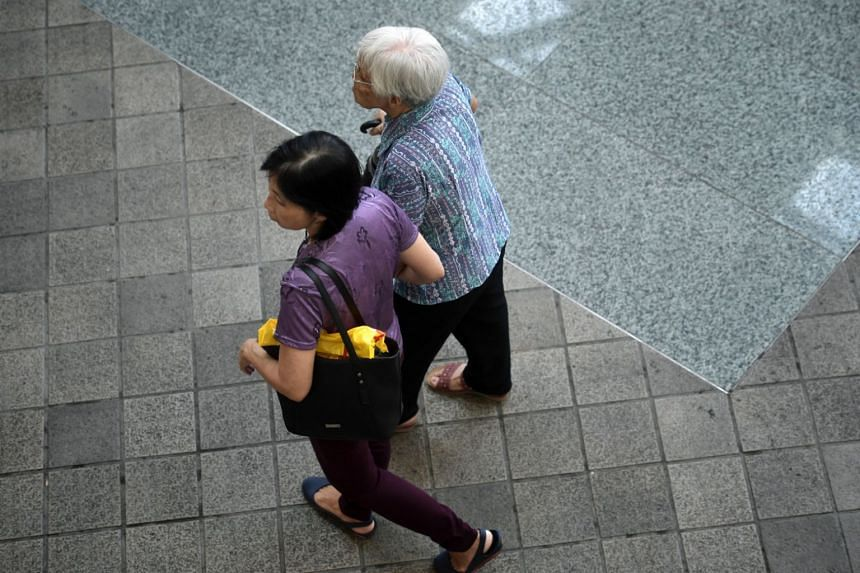 An elderly woman together with her caregiver in Toa Payoh on Oct 2, 2018.