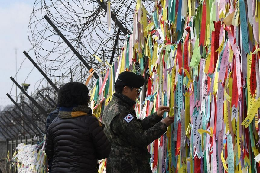 A South Korean soldier looks at ribbons with inscriptions calling for peace and reunification displayed on a military fence at the Imjingak peace park near the Demilitarised Zone dividing the two Korea's in the border city of Paju on Jan 1, 2019.