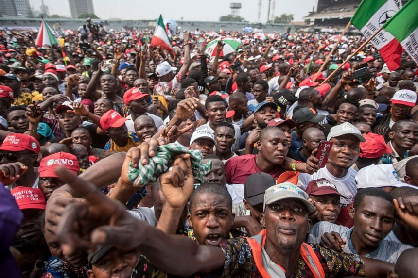 PDP supporters wave party flags as they attend a campaign rally at Tafawa Balewa square in Lagos, Feb 12, 2019.