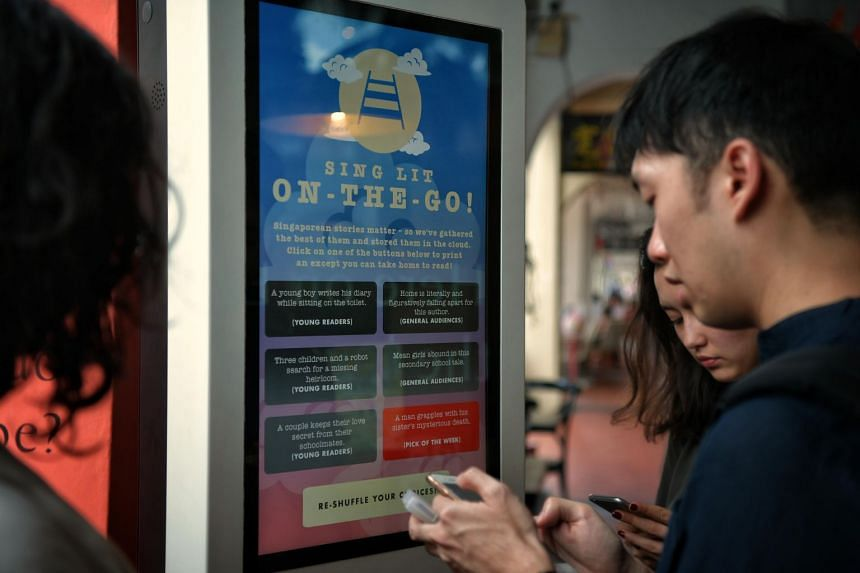 Writer Daryl Qilin Yam demonstrates how to use the Sing Lit Cloud printer, which dispenses short extracts of local literature to the public, at the media preview of the #BuySingLit movement's third edition at Chinatown bookstore The Moon on Feb 13.