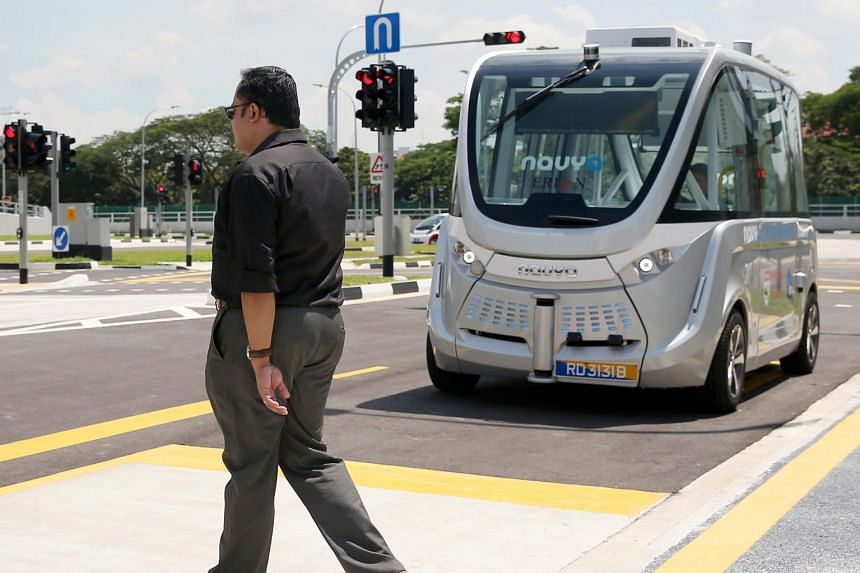 """A """"jay-walker"""" passes by the front of a Navya self-driving shuttle bus. Singapore was the top-ranking country in terms of policy and consumer acceptance of autonomous vehicles, and second in infrastructure."""