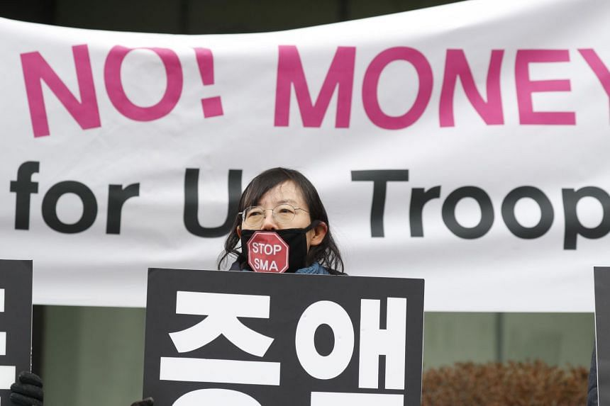 South Korean protesters shout slogans and hold banners during a rally on Jan 31 against the agreement for Seoul to pay more towards maintaining US troops in the country.