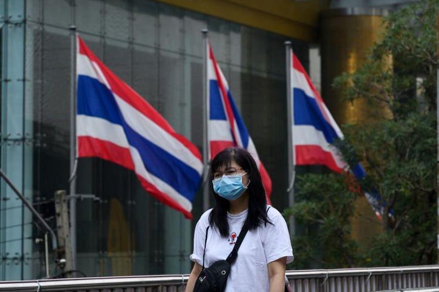 A woman wearing a face mask walks on a bridge  in Bangkok, on Feb 2, 2019.