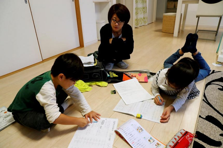 Motoko Hagiwara supervises her children doing their homework in the living room of their house at Higashinohara district in Inzai, Chiba Prefecture, Japan, on Nov 6, 2018.