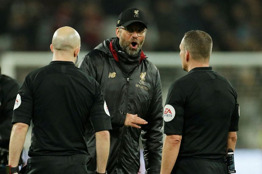 Klopp speaking with referee Kevin Friend after the match.