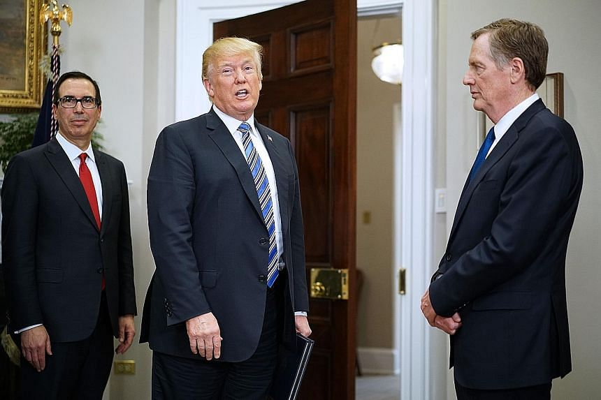 US Treasury Secretary Steven Mnuchin (left) and Trade Representative Robert Lighthizer flanking President Donald Trump. The two Trump officials are scheduled to meet President Xi Jinping in Beijing tomorrow. Mr Trump has indicated a willingness to gi
