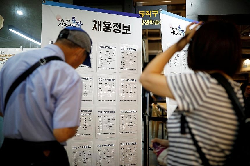 Job seekers looking at advertisements at a job fair in Seoul last year. The unemployment rate rose to 4.4 per cent last month, the highest since January 2010, with most of the job losses seen in manufacturing and construction sectors, data from Stati