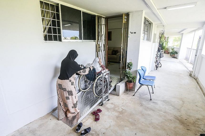 Ms Diana Norahman helping her mother up a customised fixed ramp installed at their HDB flat entrance. While the Government is looking at building more integrated developments, many seniors prefer to age in familiar surroundings, noted Senior Parliame