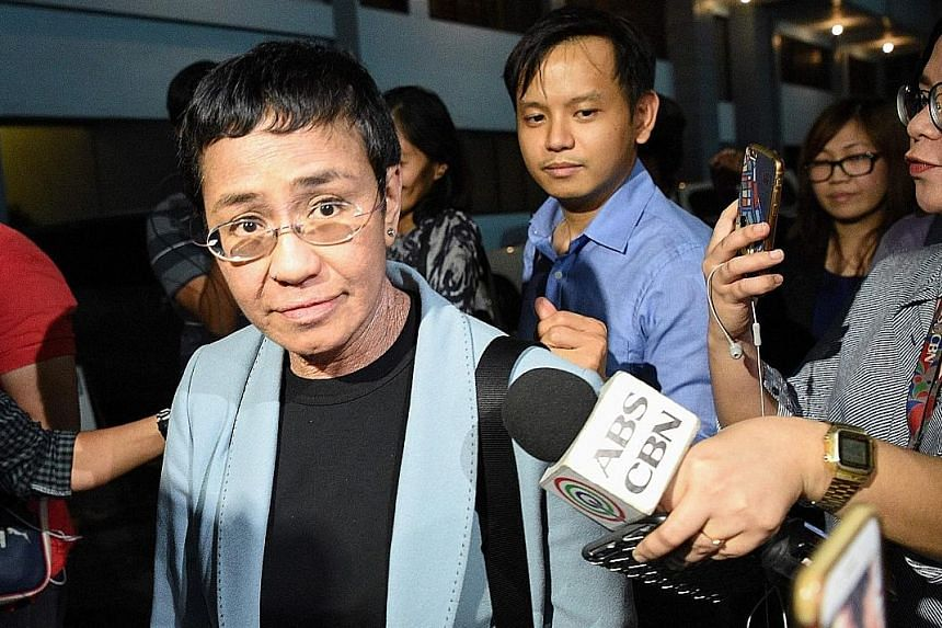 Philippine journalist Maria Ressa being surrounded by the media after her arrest in Manila yesterday on a cyber libel complaint.