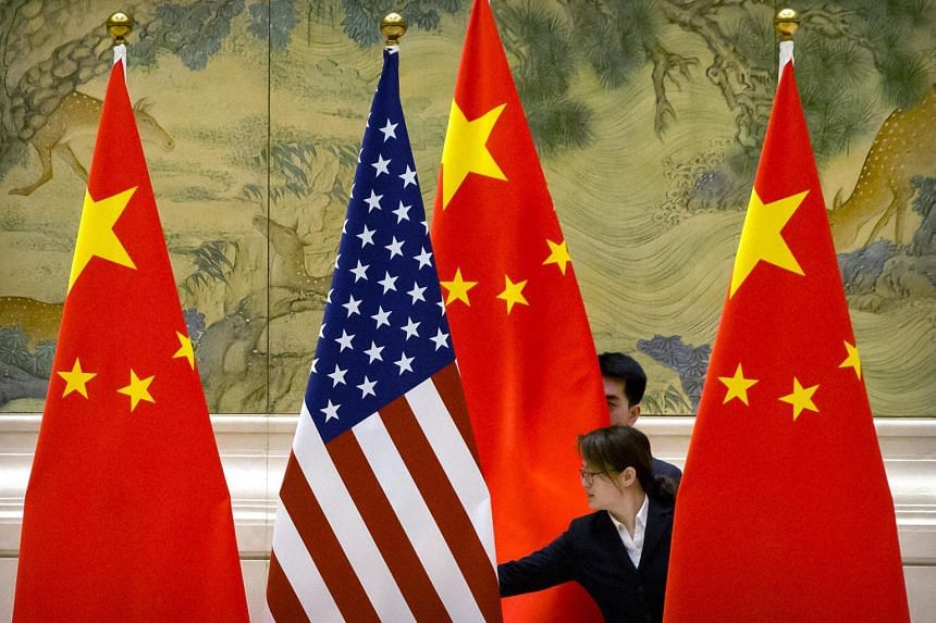 Chinese staff adjust the US and Chinese flags before trade talks at the Diaoyutai State Guesthouse in Beijing, China, on Feb 14, 2019.