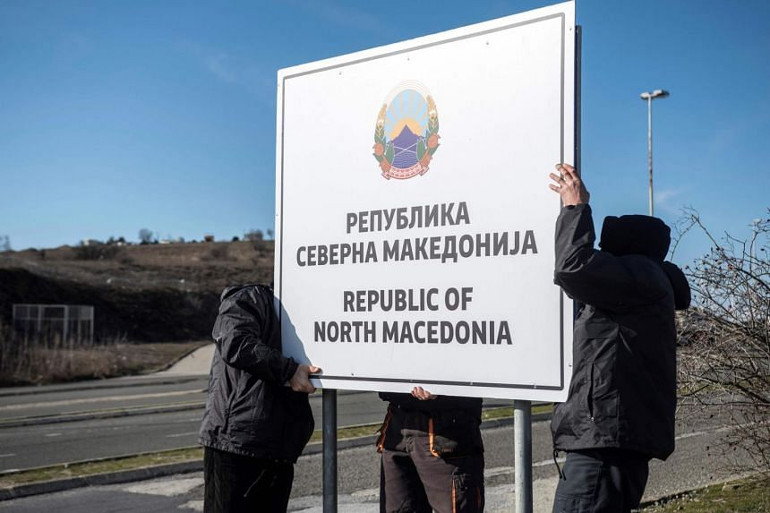 Workers set up a sign reading 'Republic of North Macedonia' at the Macedonia-Greece border near Gevgelija on Feb 13, 2019.