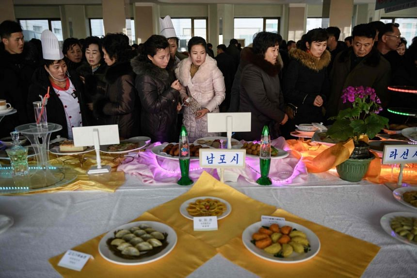 Visitors look at dishes made using potato flour at North Korea's national cooking competition in Pyongyang on Feb 13, 2019.