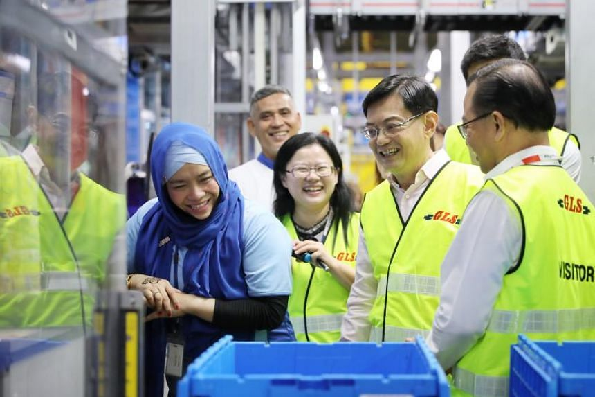 Finance Minister Heng Swee Keat (second from right) and FairPrice CEO Seah Kian Peng (right) speaking to Autostore picker Norliati binte Othman (in blue) at the FairPrice Hub in Benoi.