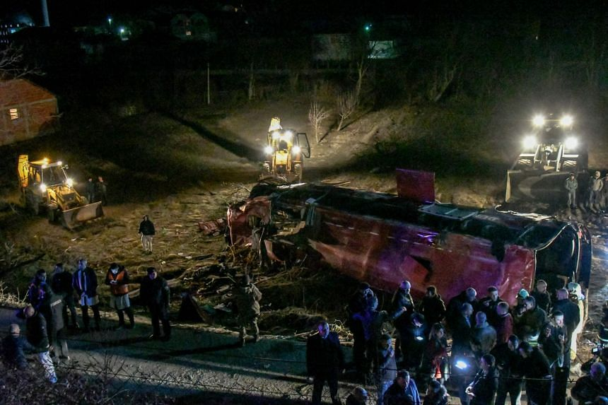 Bystanders and rescue personnel gather near the wreckage of the bus.