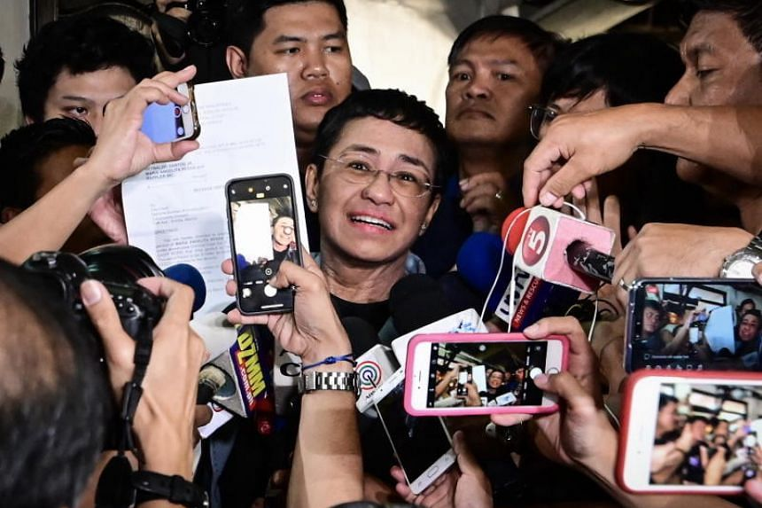 Maria Ressa (C), CEO and Executive Editor of online news site Rappler and President of Rappler Holdings Corporation, displays her release order after posting bail on her cyber libel case at a local court in Manila, Philippines, 14 February 2019. Acco