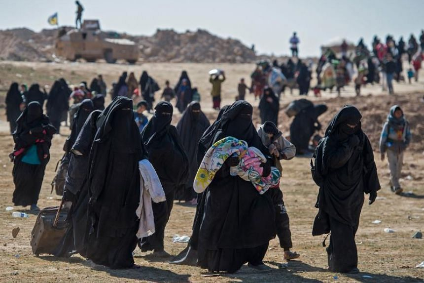 Fully veiled women and children fleeing from the Baghouz area in the eastern Syria walk in a field on Feb 12, 2019 during an operation by the US-backed forces to expel hundreds of Islamic State group jihadists from the region.