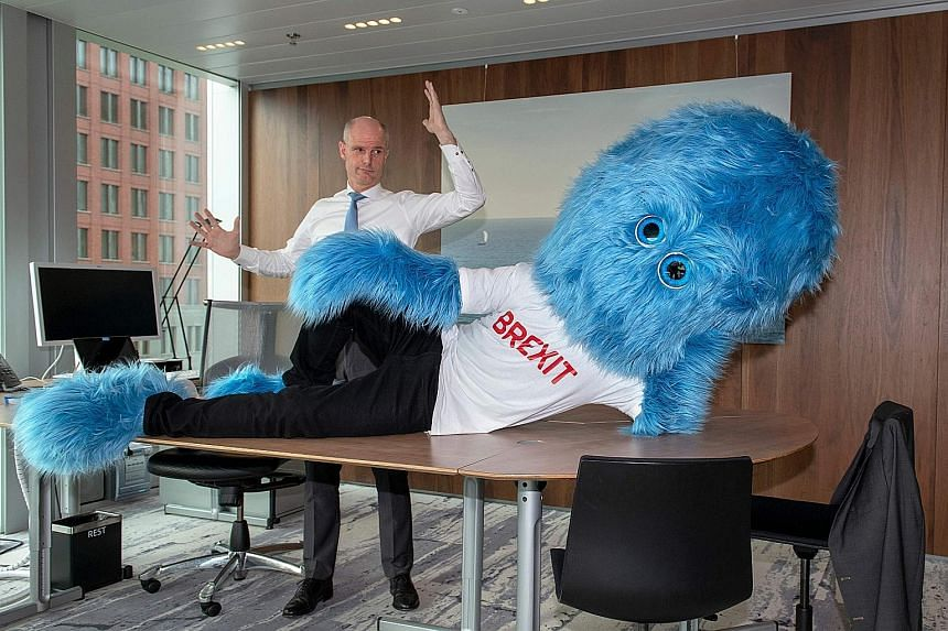 "Netherlands Foreign Minister Stef Blok gesturing next to ""the Brexit monster"" in his office in The Hague. The Dutch government has unveiled its own vision of Brexit in the form of a big, blue and hairy monster."