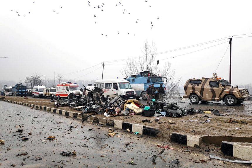 Indian soldiers examine the debris after an explosion in Lethpora in South Kashmir's Pulwama district on Feb 14, 2019.